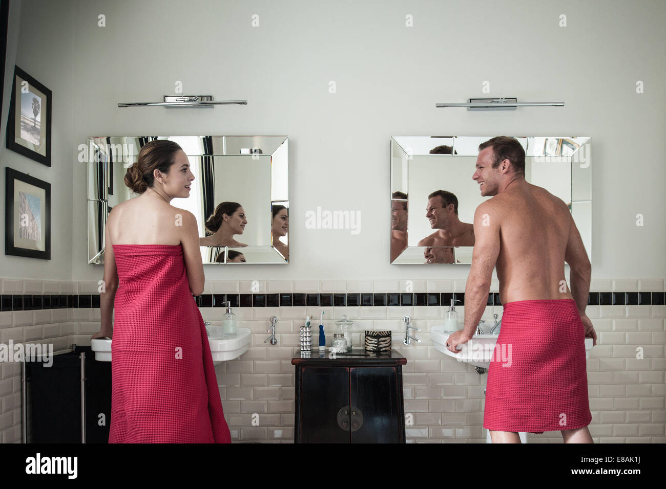 Young couple at sinks in his and hers bathroom - Stock Image