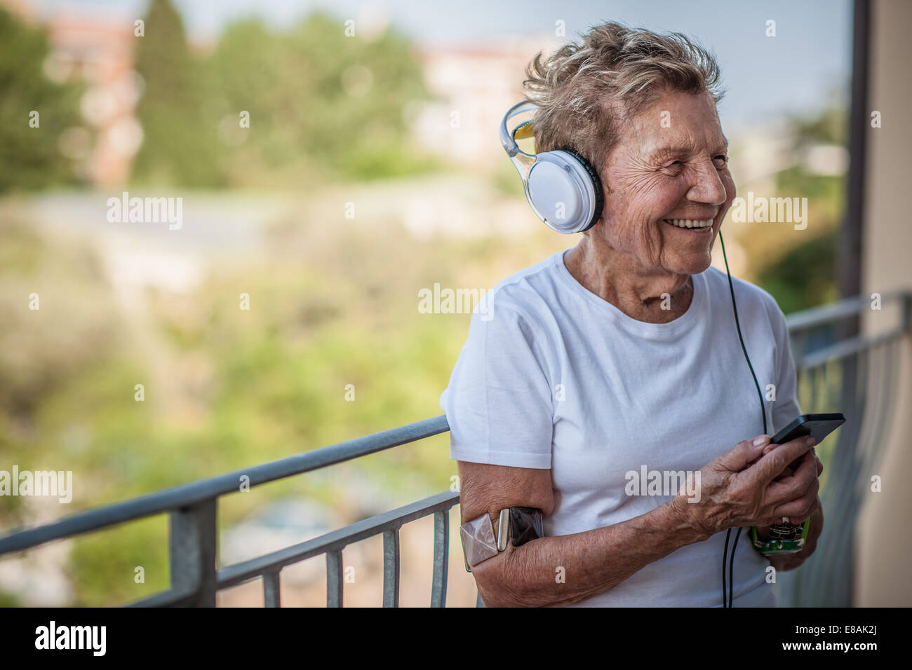 A very senior woman listening to music on headphones on apartment balcony - Stock Image