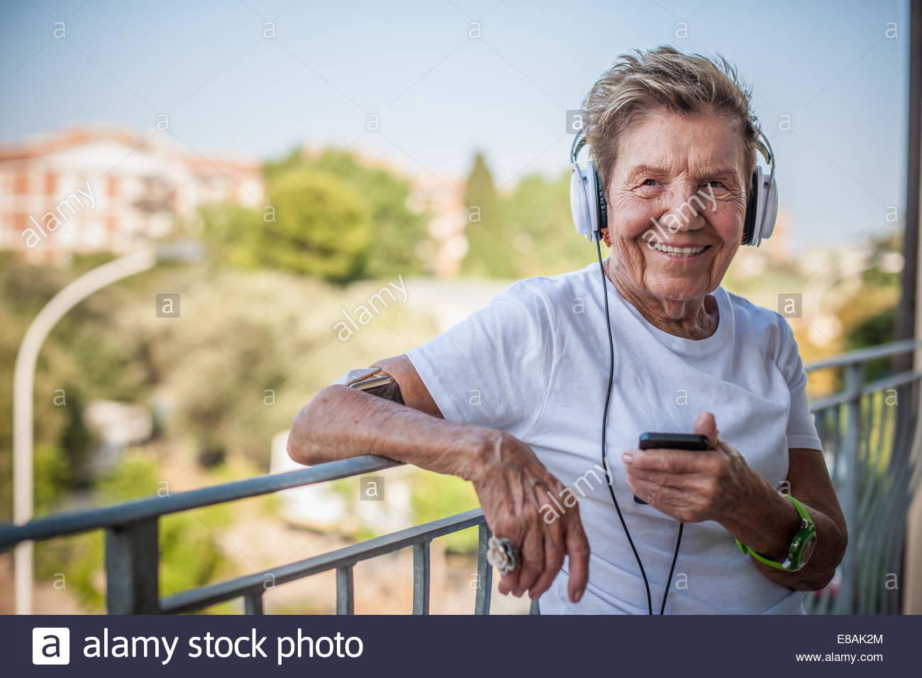 Portrait of a very senior woman leaning on balcony listening to headphones - Stock Image