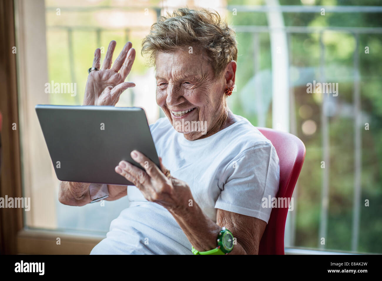 A very senior woman using digital tablet on apartment balcony - Stock Image