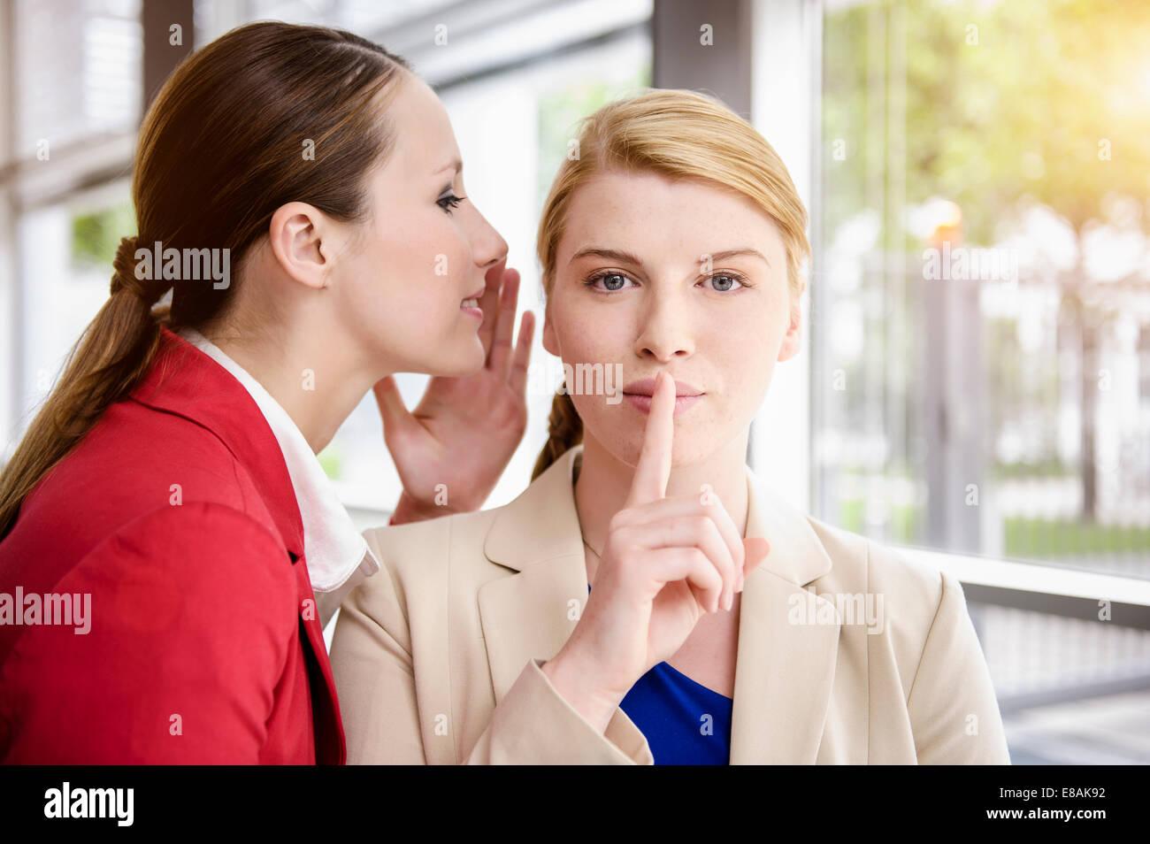 Businesswomen sharing secret - Stock Image