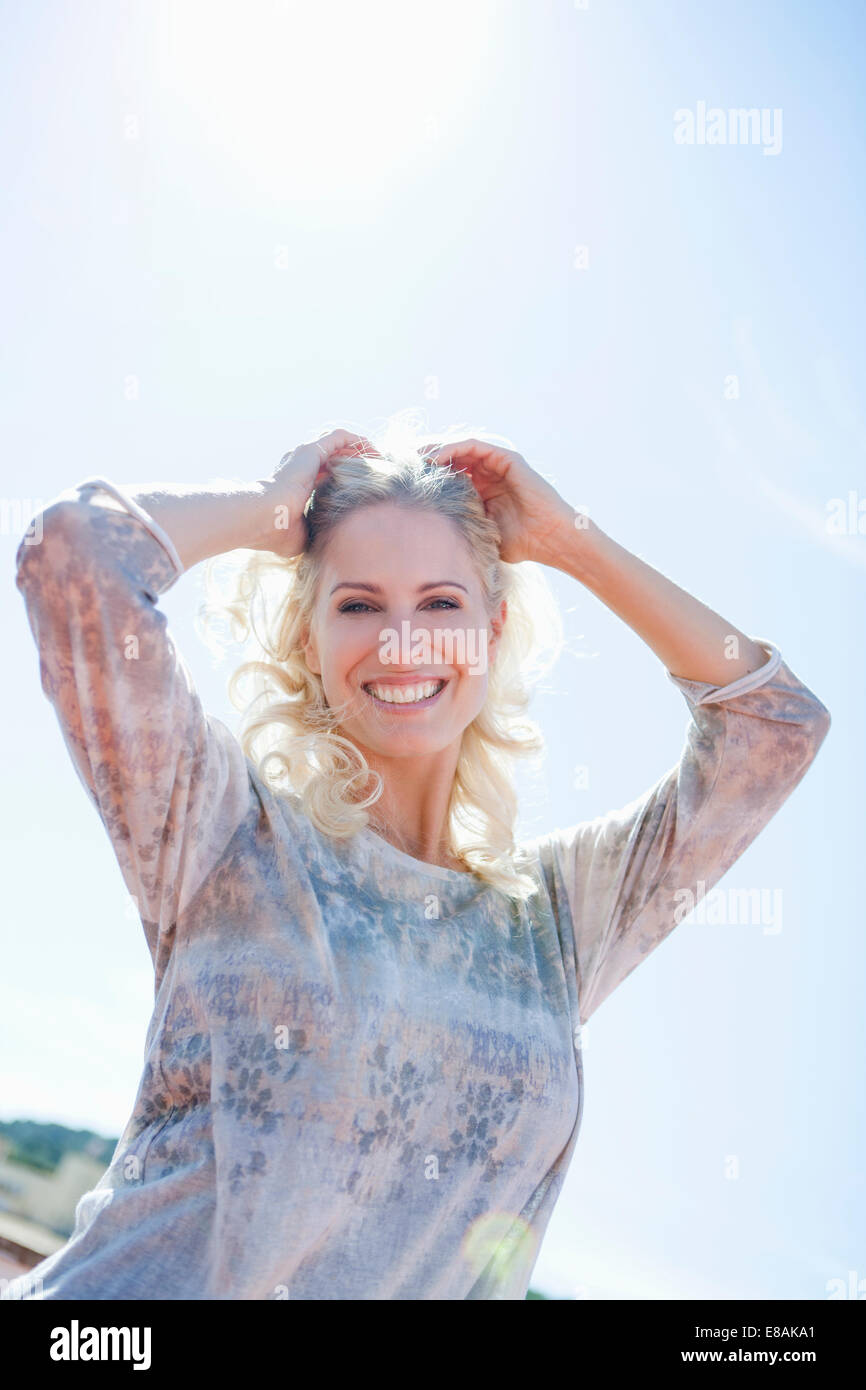 Woman posing against sunny sky - Stock Image