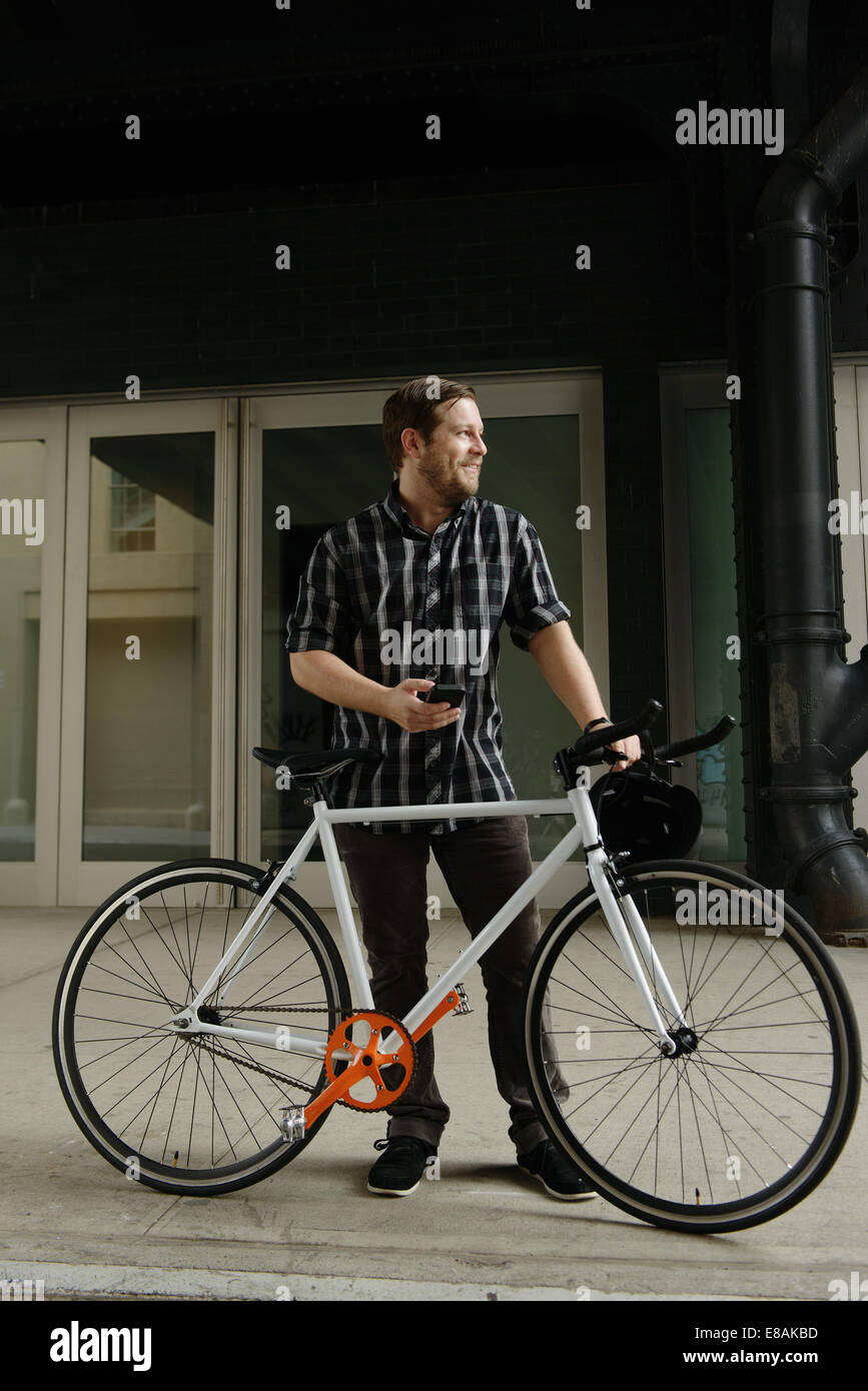 Male cycle messenger checking directions on smartphone outside office - Stock Image