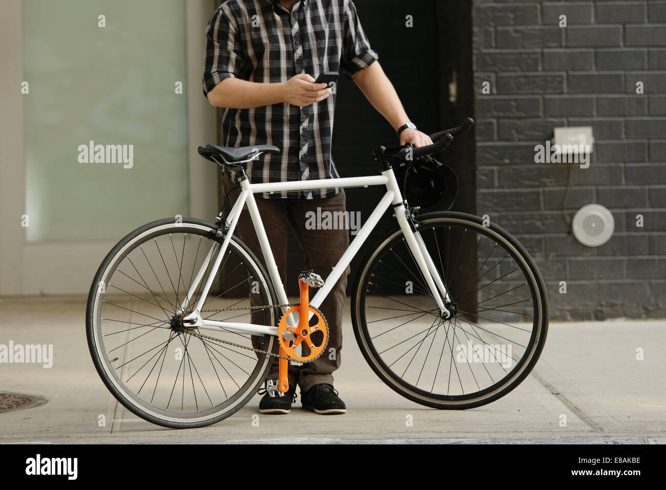 Neck down view of male cycle messenger checking directions on smartphone outside office Stock Photo