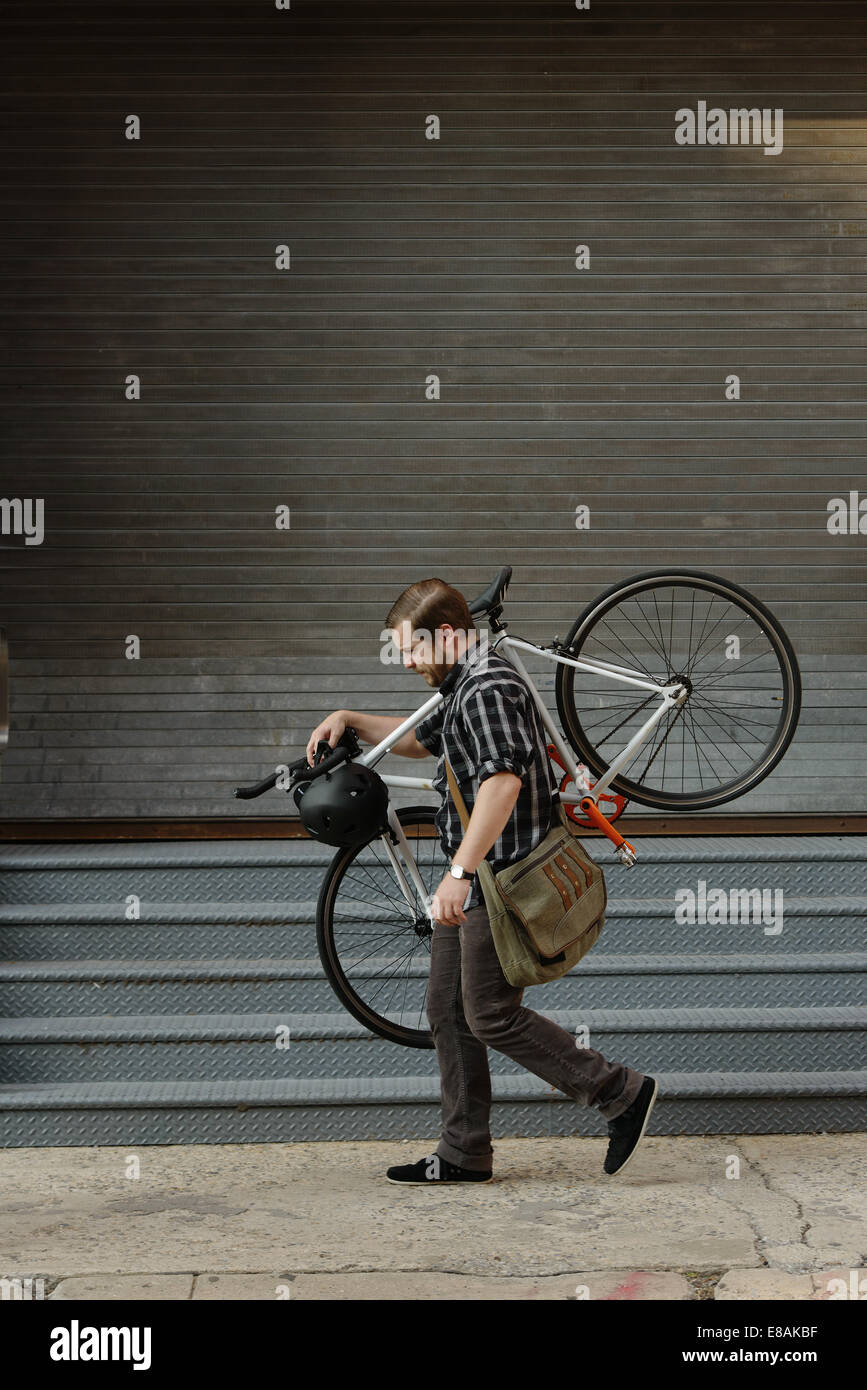 Male cycle messenger carrying cycle on sidewalk - Stock Image
