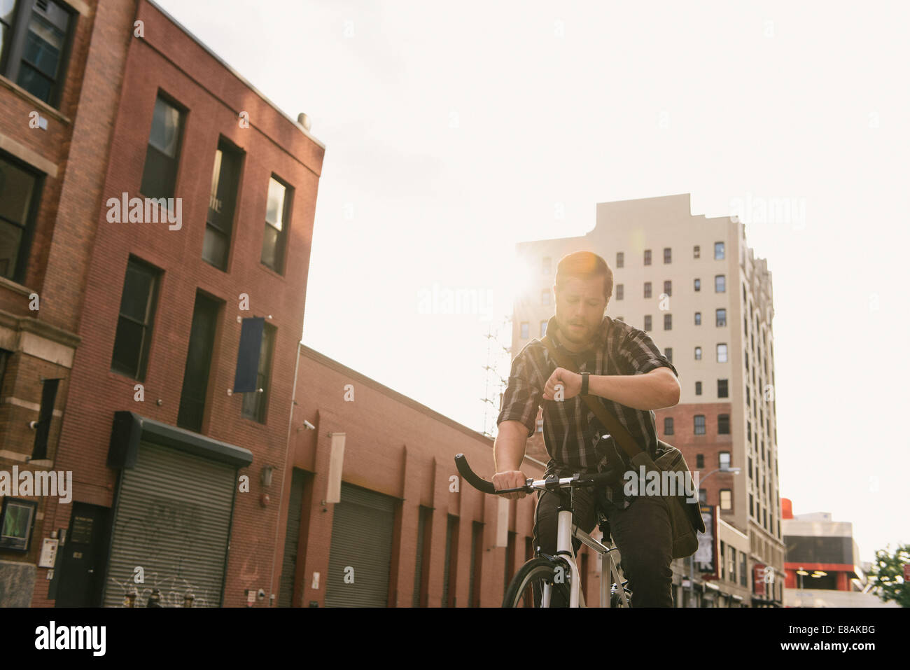Male cycle messenger checking time on wristwatch - Stock Image
