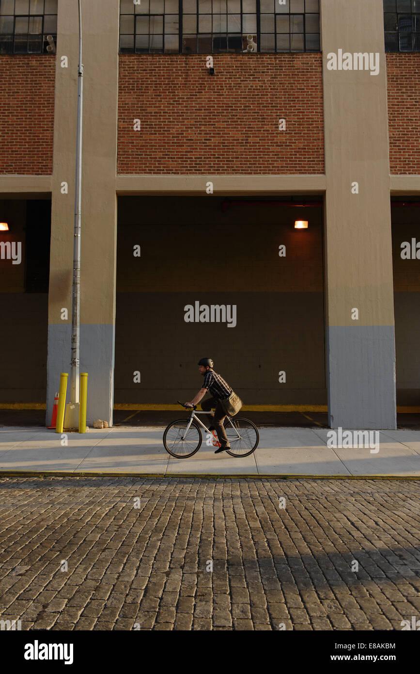 Male messenger cycling along city sidewalk - Stock Image