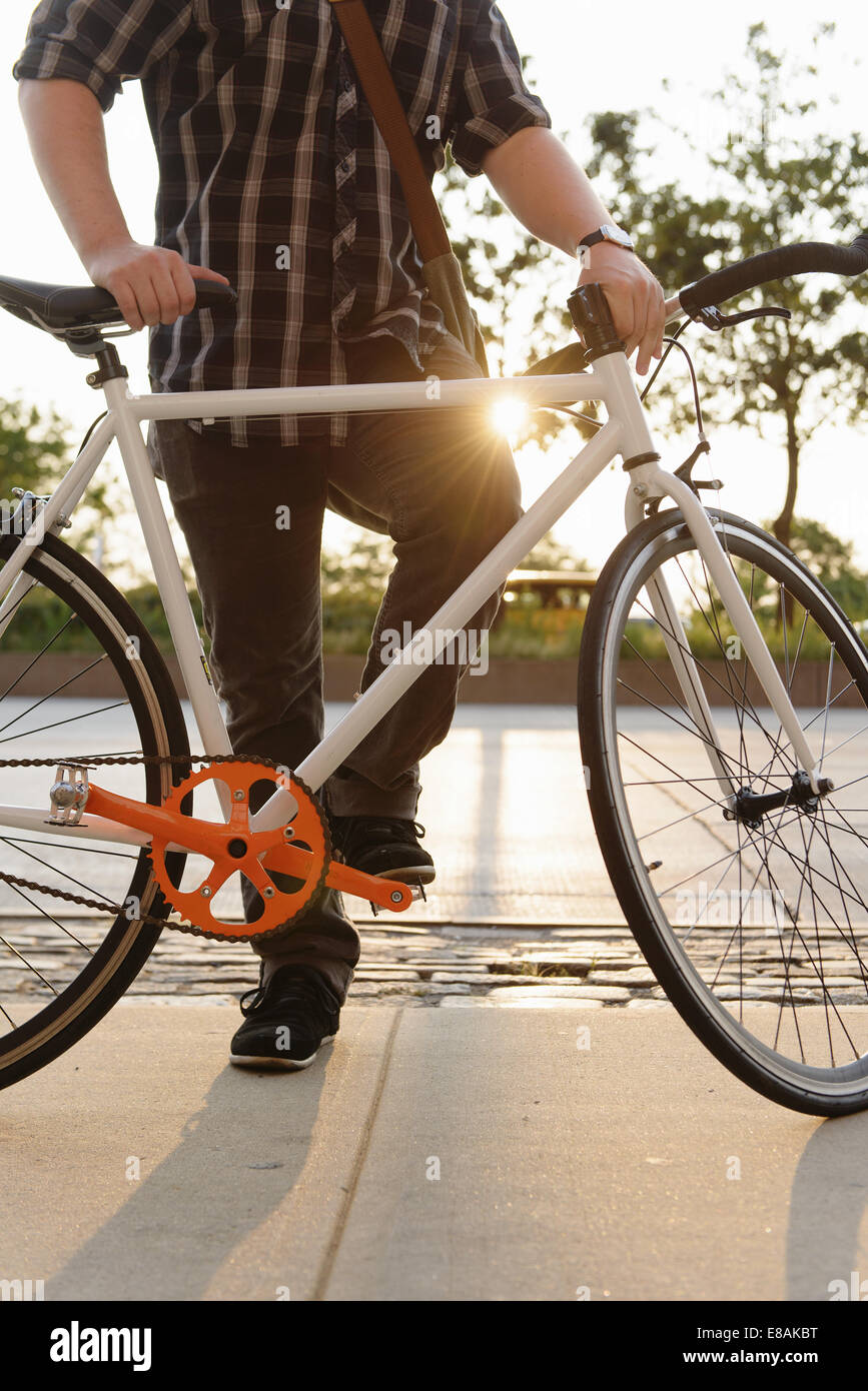 Neck down view of male cycle messenger taking a break - Stock Image
