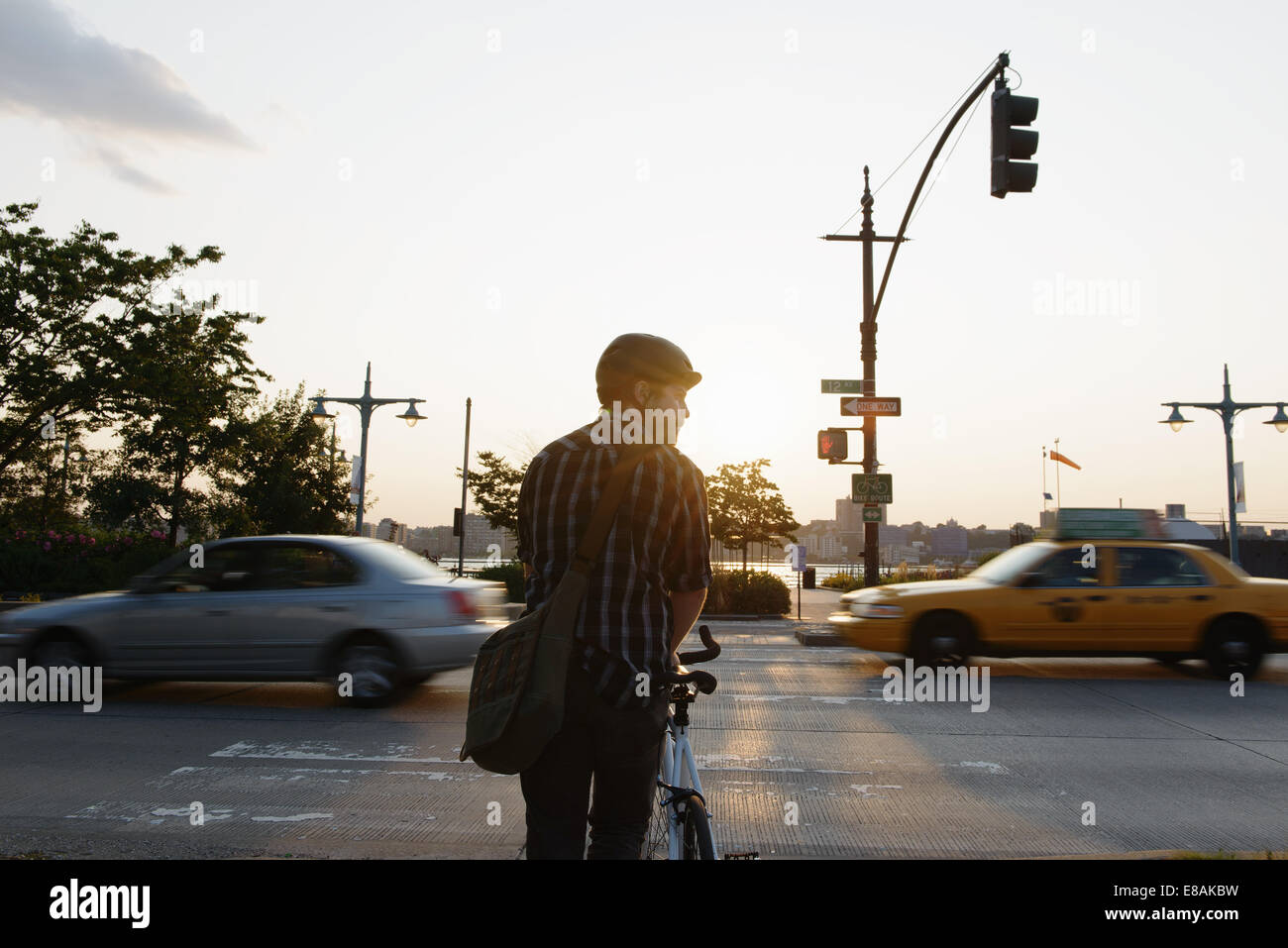 Male cycle messenger waiting to cross busy road - Stock Image