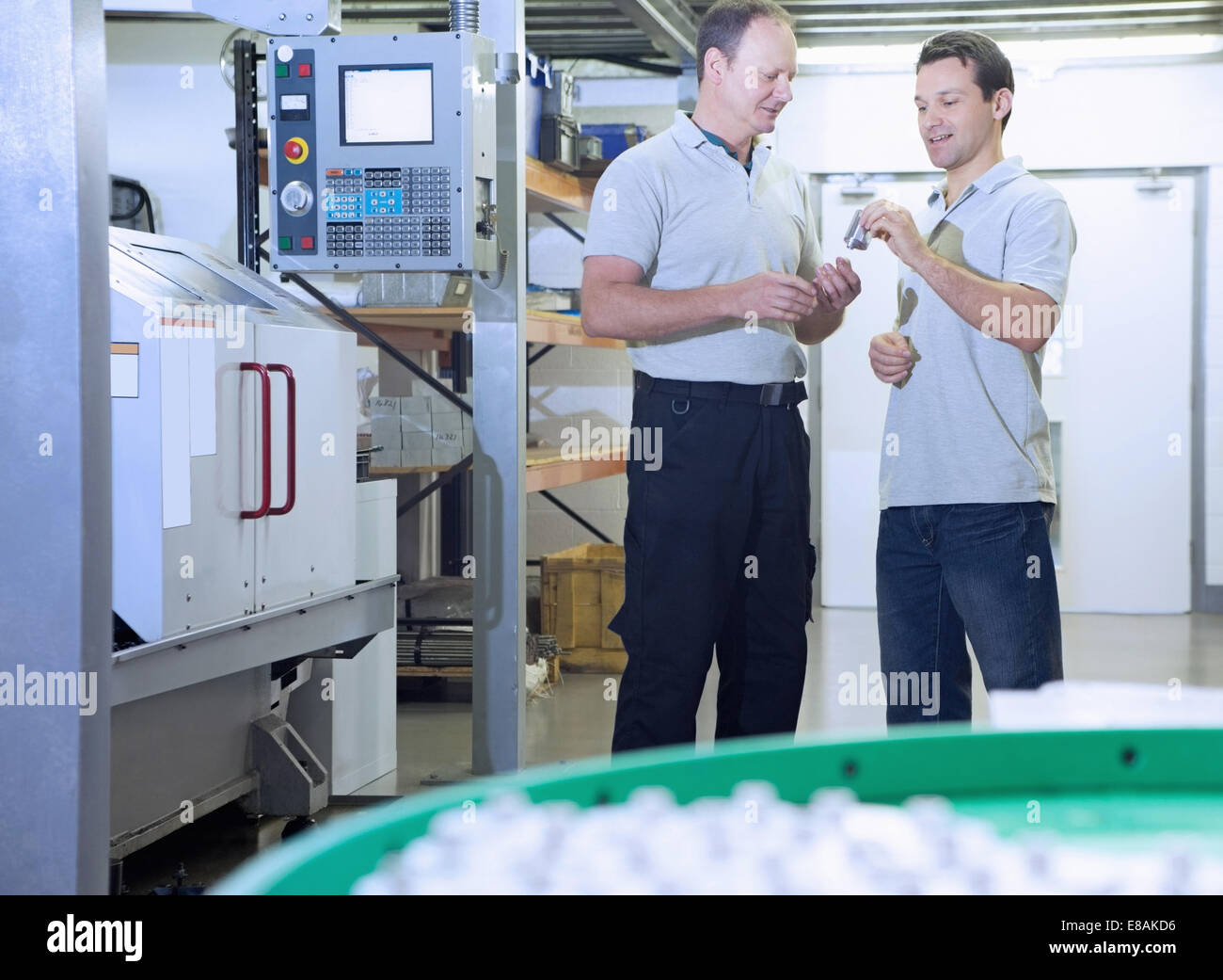 Engineers in discussion in CNC precision engineering centre - Stock Image