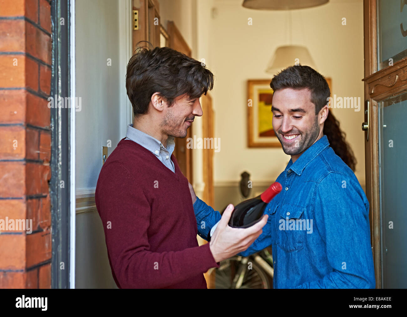 Men with bottle of wine smiling at front door - Stock Image