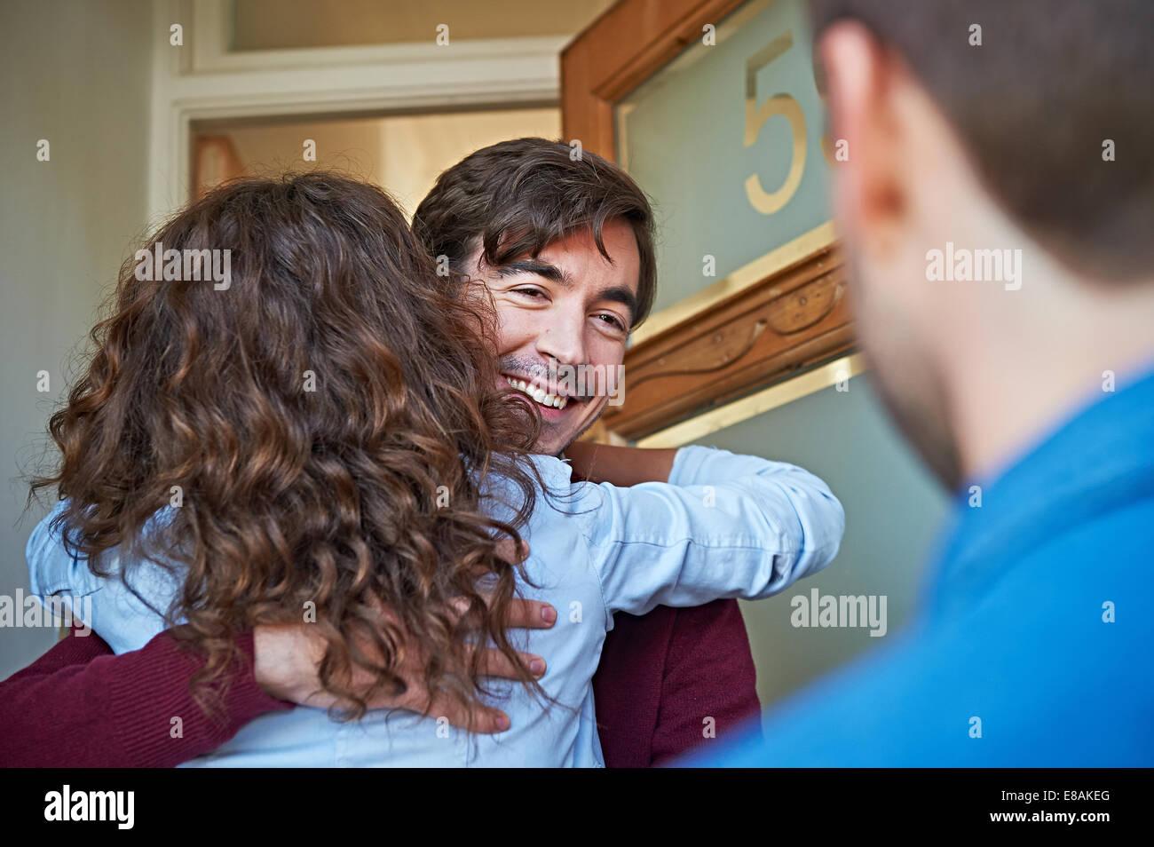 Man welcoming friends at front door - Stock Image