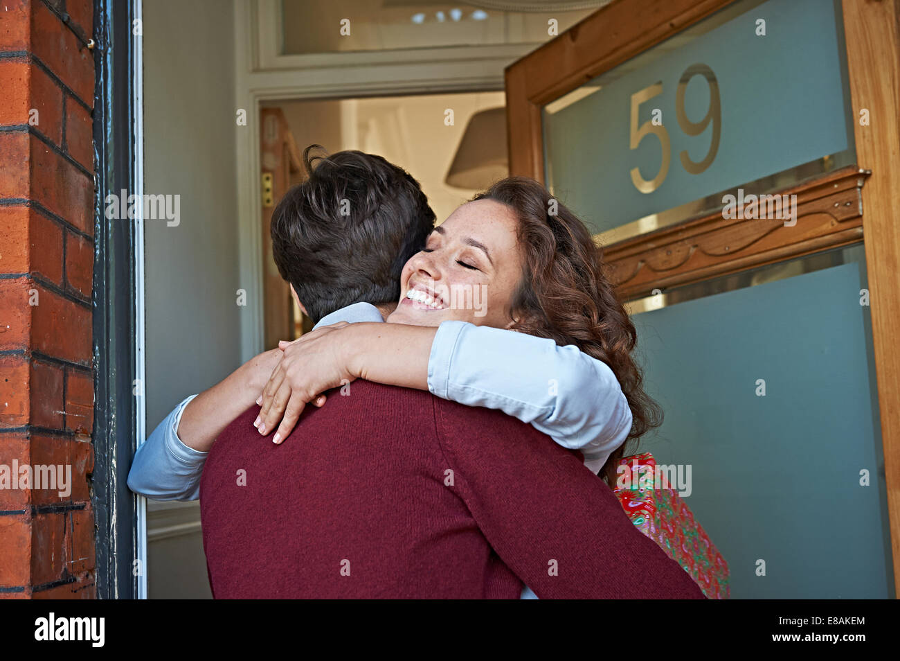 Couple hugging at front door - Stock Image