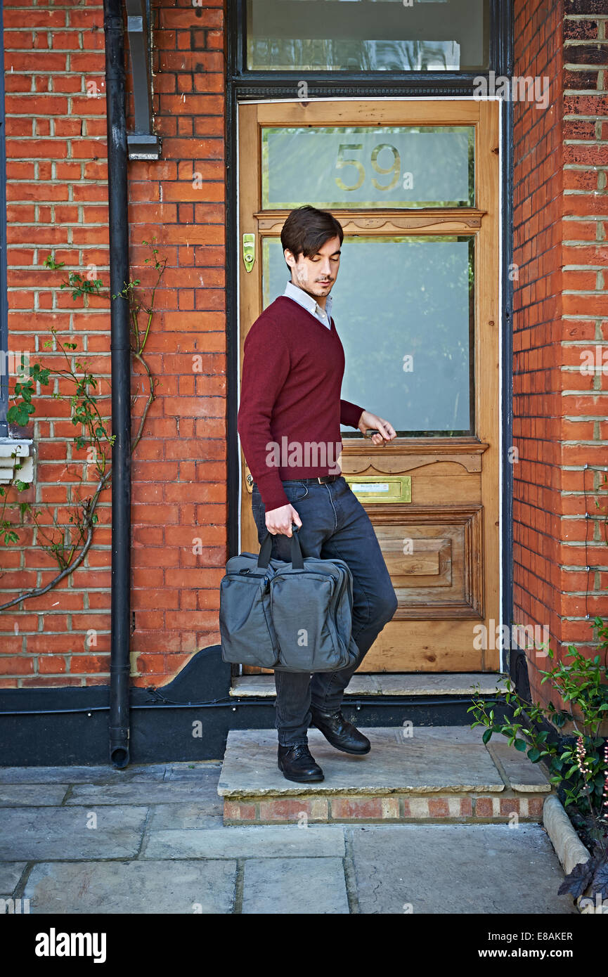 Man stepping out of front door - Stock Image