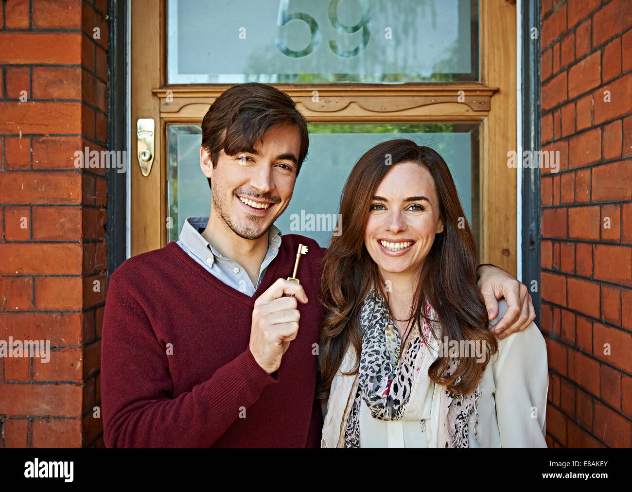 Couple delighted with key to house - Stock Image