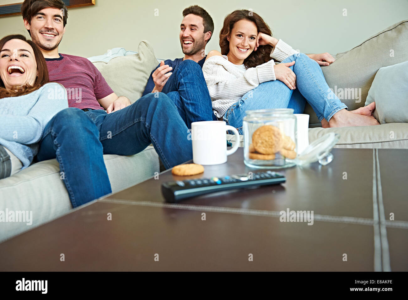 Group of friends watching sport in living room - Stock Image
