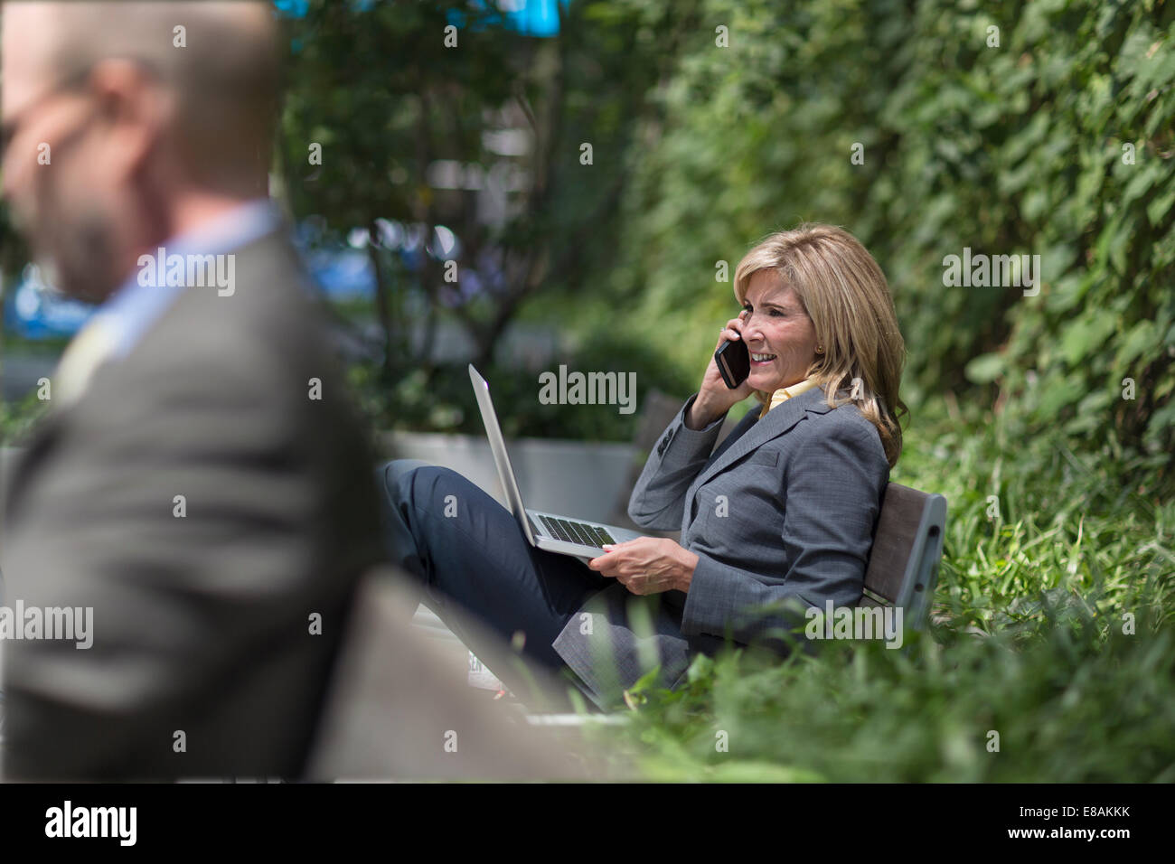 Mature businesswoman on phone with laptop - Stock Image