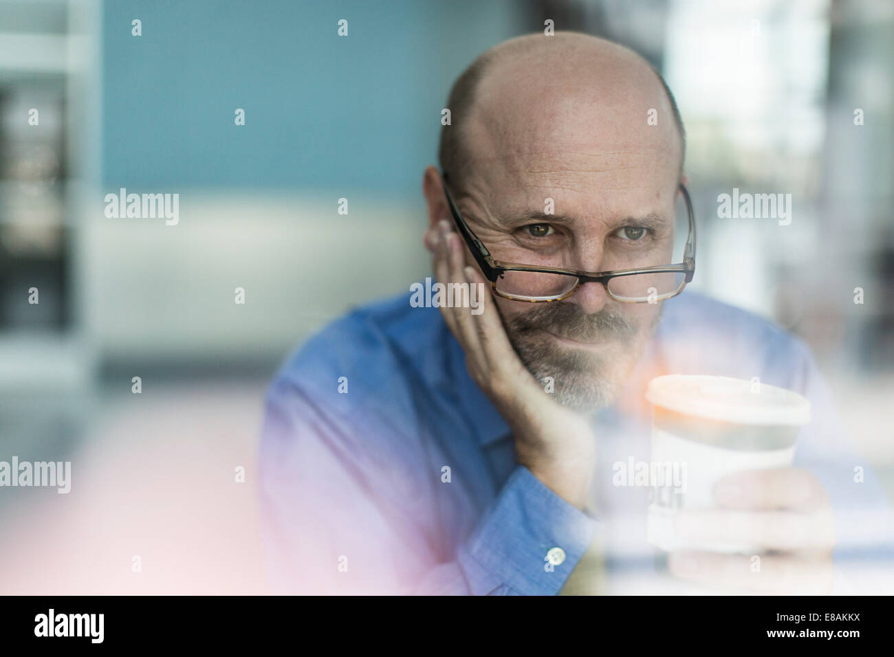 Mature businessman wearing glasses with coffee - Stock Image