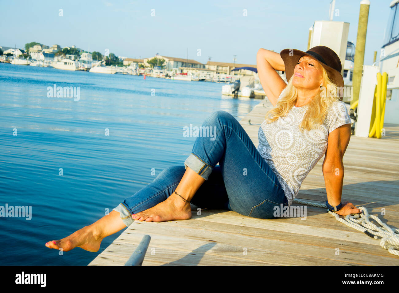 Mature woman sitting on harbor pier with eyes closed, Monmouth Beach, New Jersey, USA Stock Photo