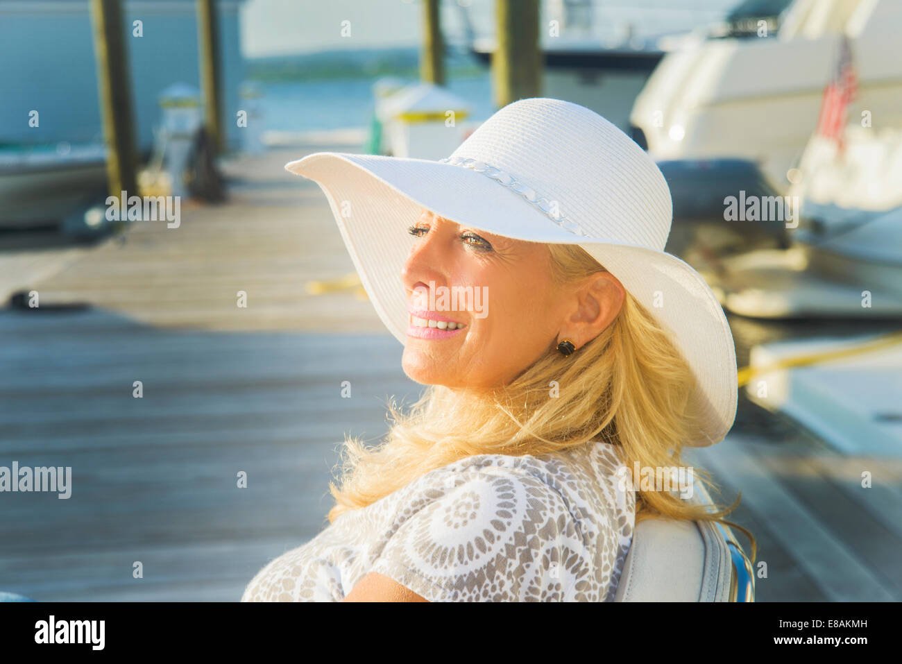 Mature woman sitting on harbor pier, Monmouth Beach, New Jersey, USA - Stock Image