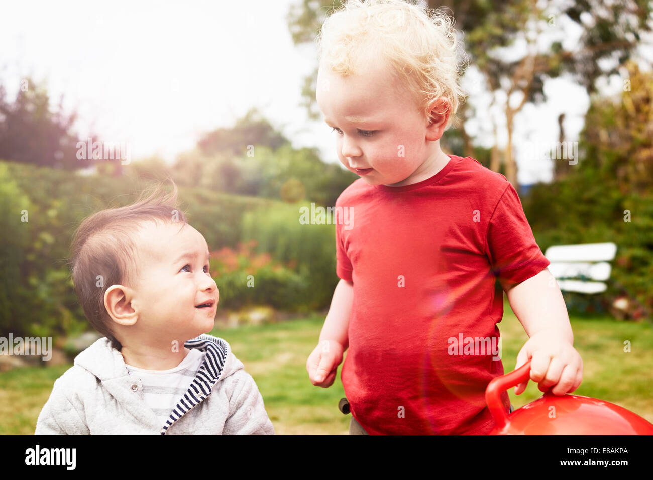 Two baby boys looking at each other - Stock Image