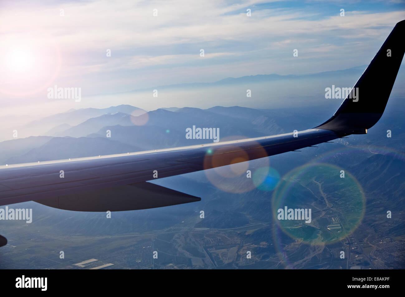 Aeroplane wing flying over landscape - Stock Image