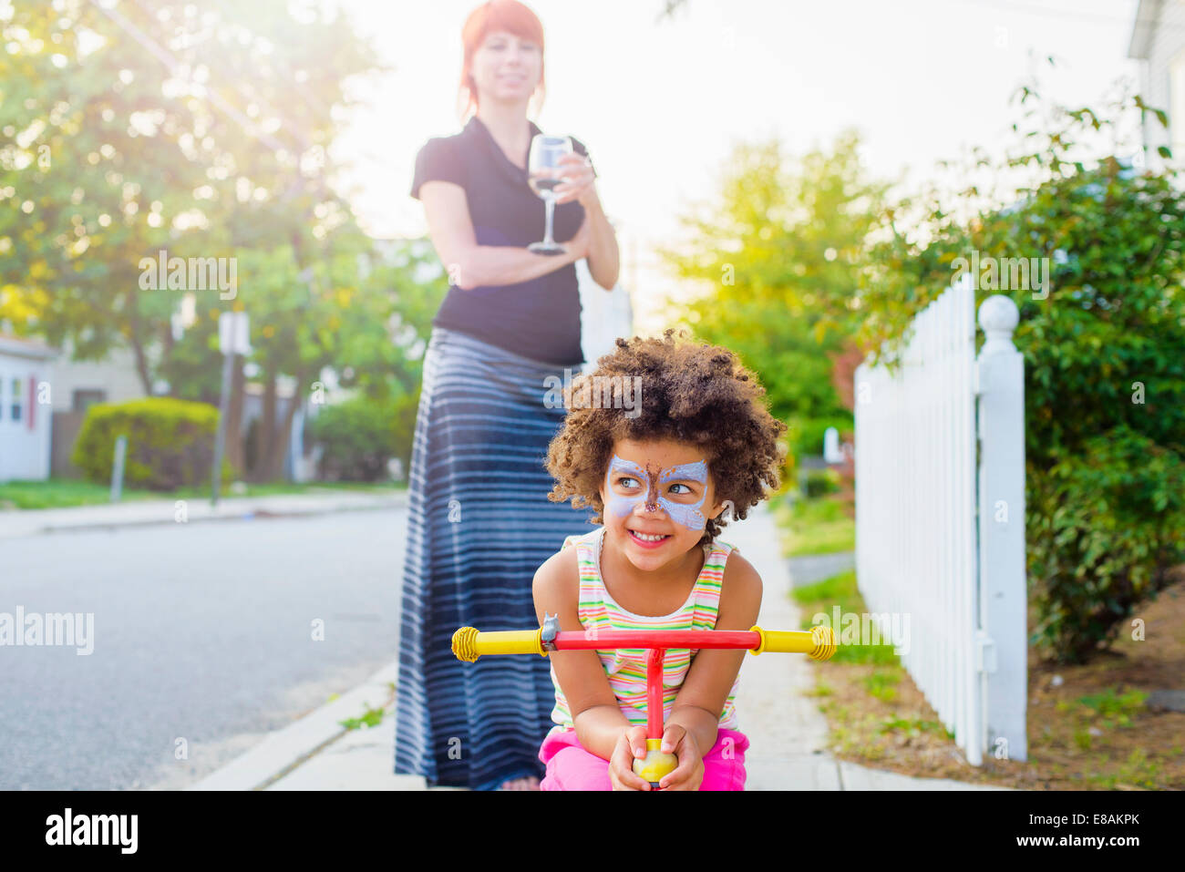 Girl with painted face crouching on scooter on suburban street - Stock Image