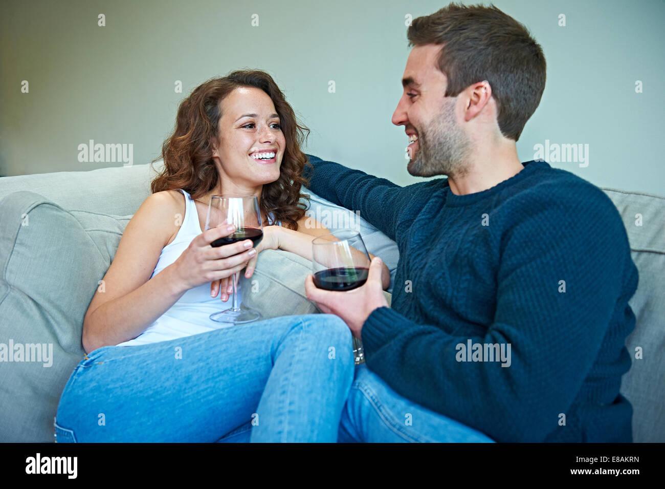 Couple enjoying wine on sofa - Stock Image