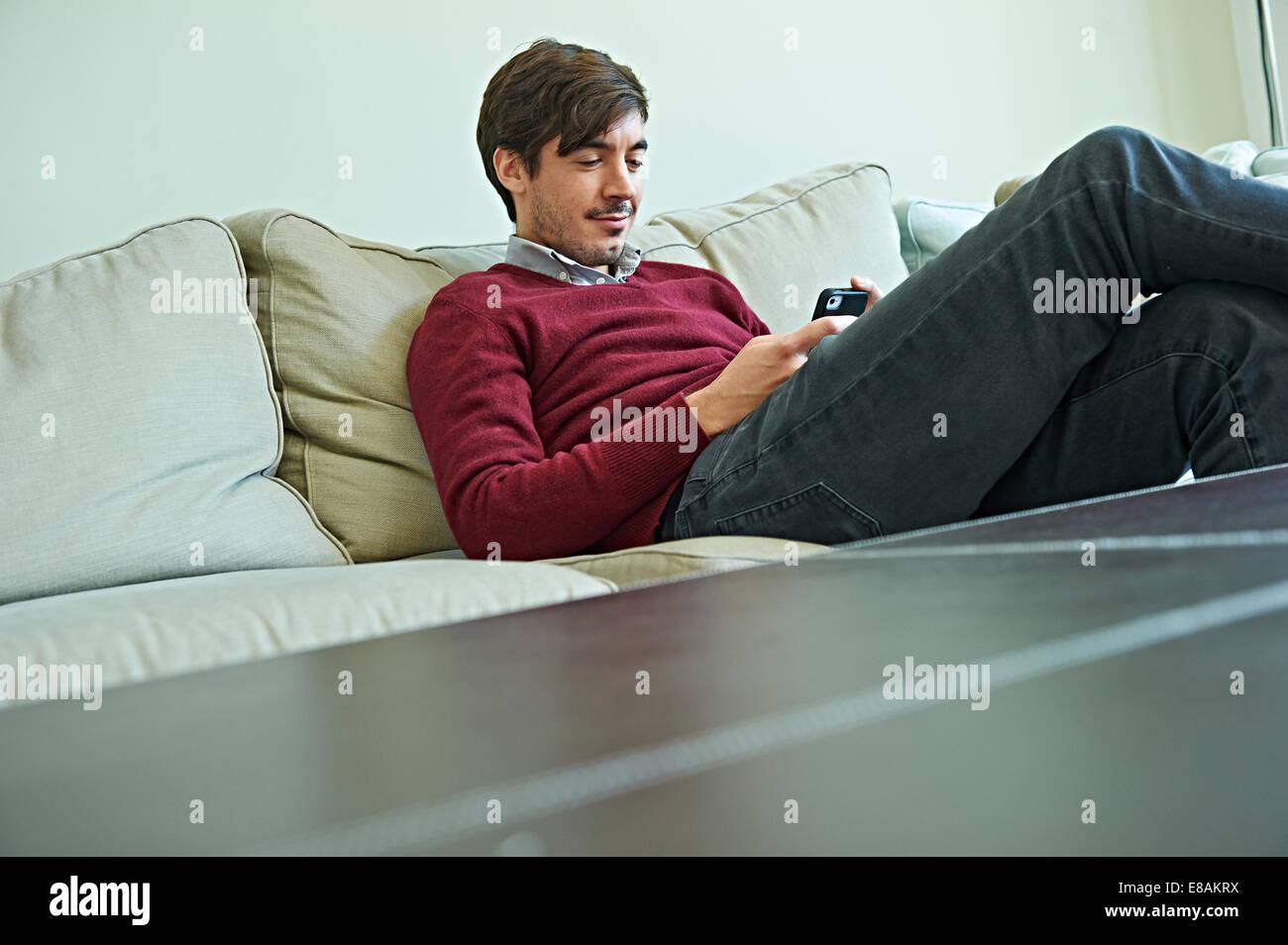 Man using smartphone on sofa - Stock Image
