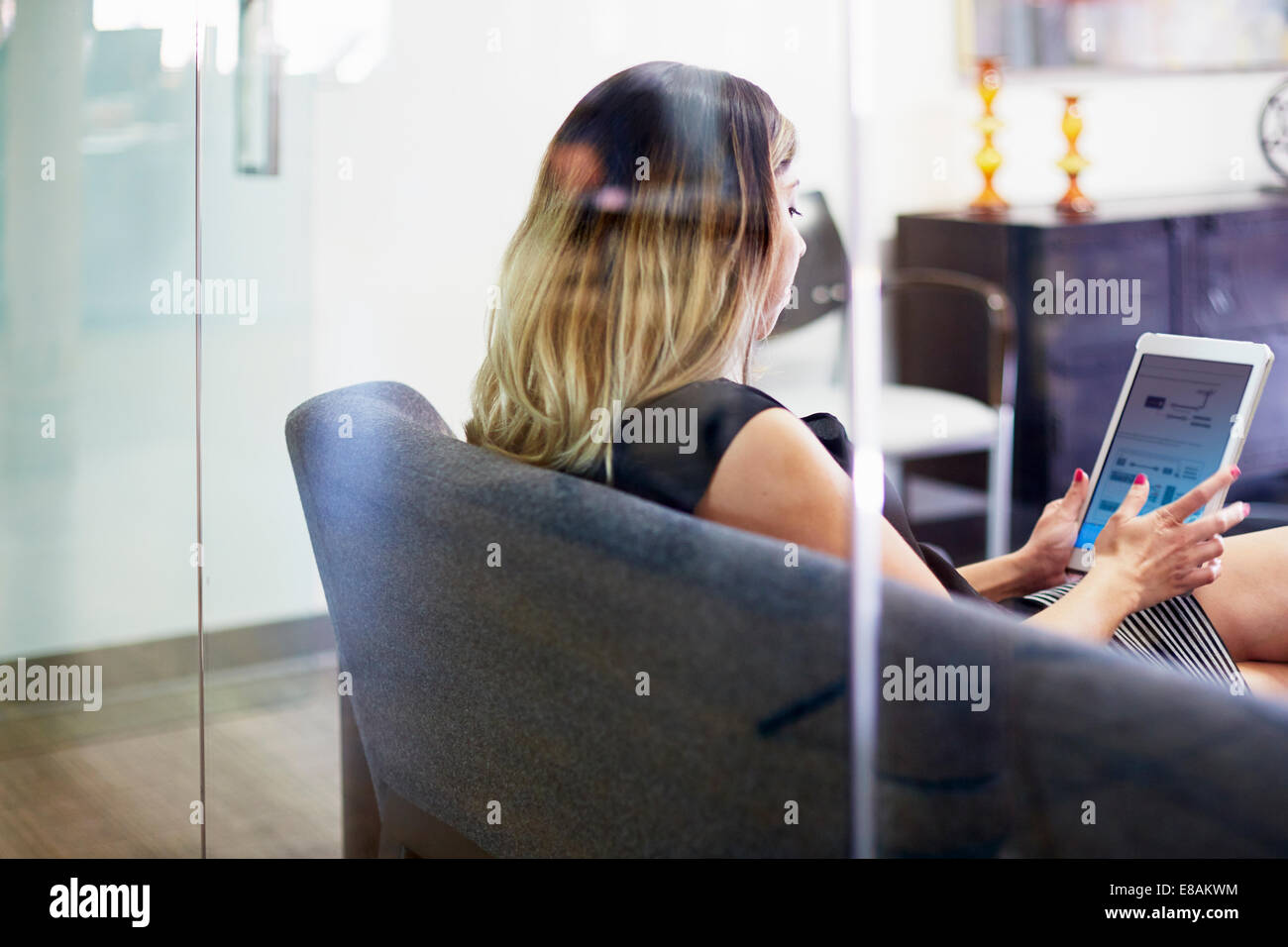 Young woman on sofa using tablet - Stock Image