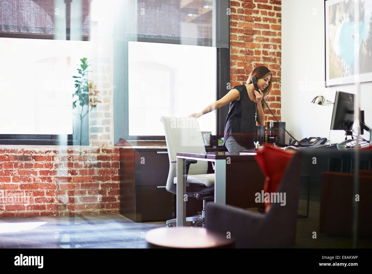 Young woman using telephone in office - Stock Image