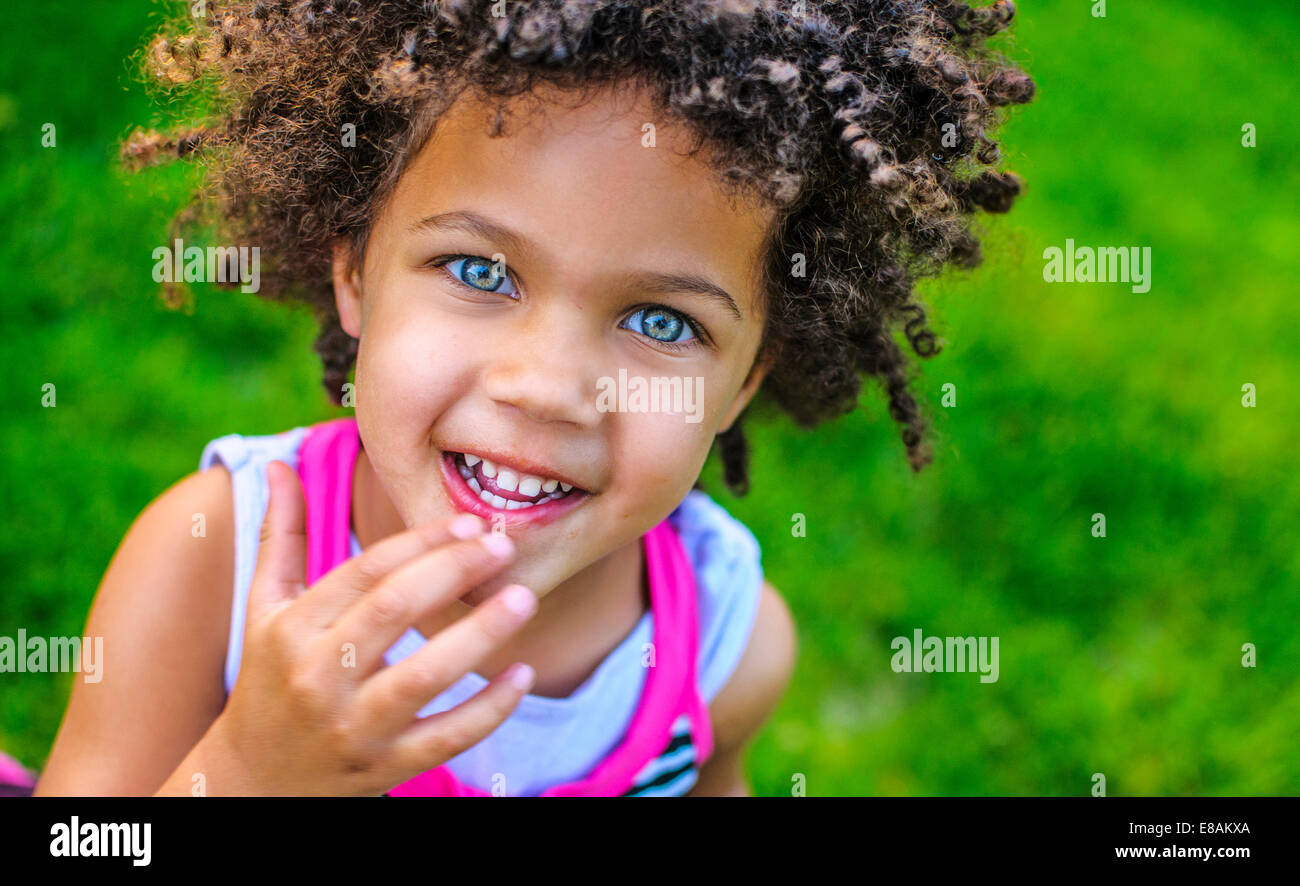 Close up portrait of girl with hand on her mouth - Stock Image