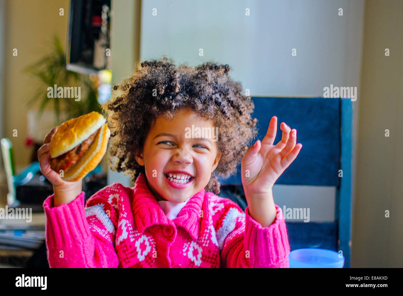 Cute girl laughing and holding up hamburger in kitchen - Stock Image