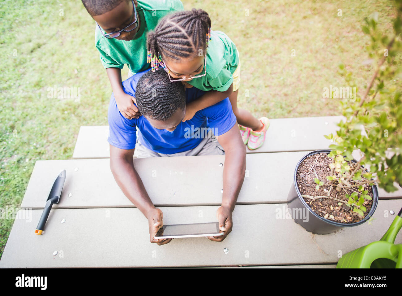 High angle view of father looking at digital tablet with daughter and son at eco camp - Stock Image