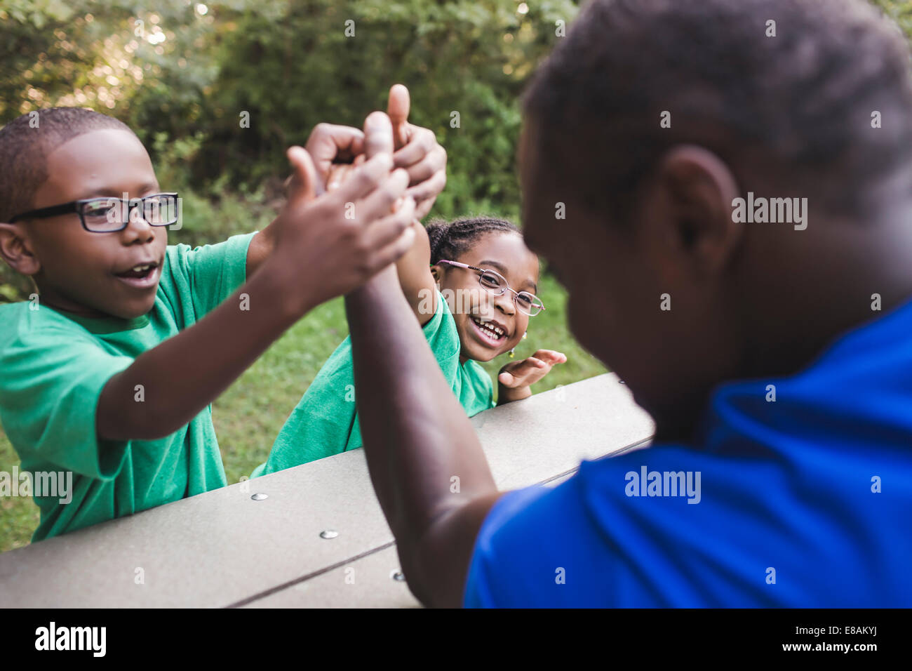 Father arm wrestling with son and daughter at parkland eco camp - Stock Image
