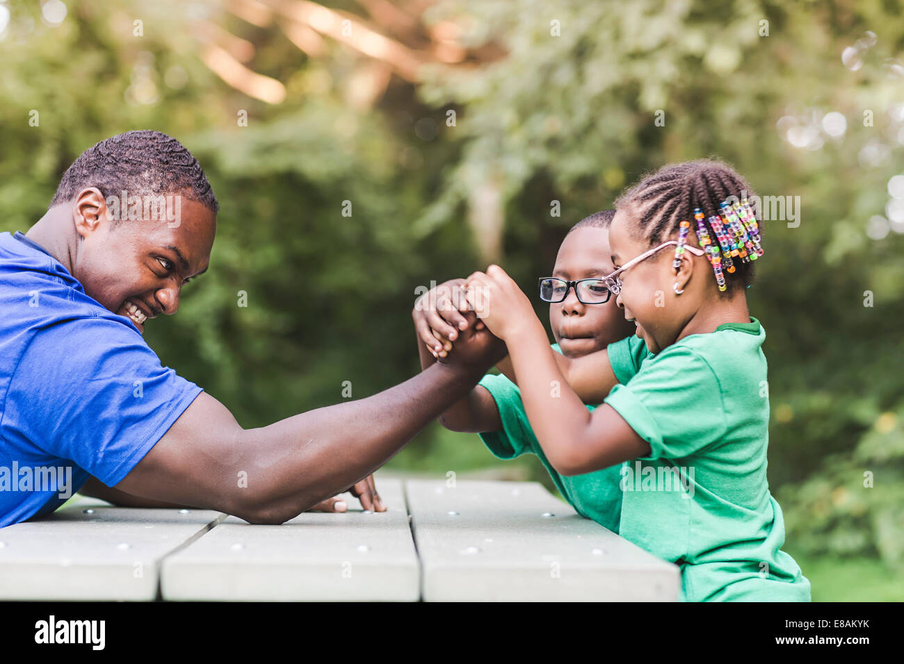 Father arm wrestling with daughter at parkland eco camp - Stock Image
