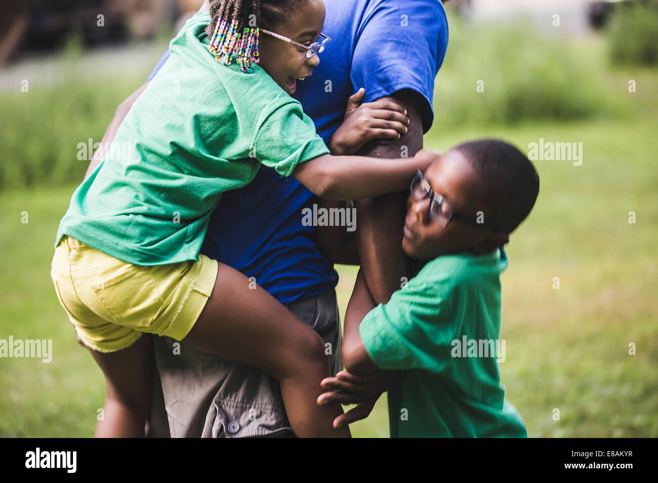Son and daughter play fighting father at parkland eco camp - Stock Image