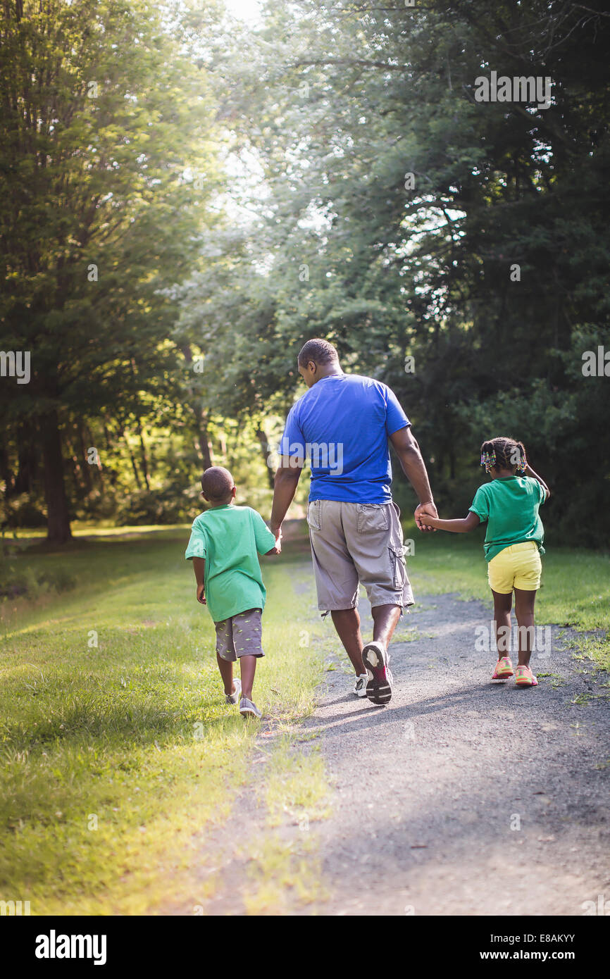 Rear view of father holding hands with son and daughter at parkland eco camp - Stock Image