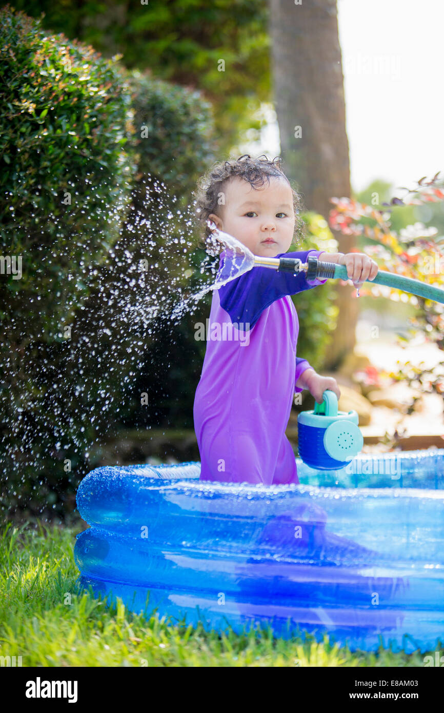 Candid portrait of a baby girl with hosepipe in paddling pool - Stock Image