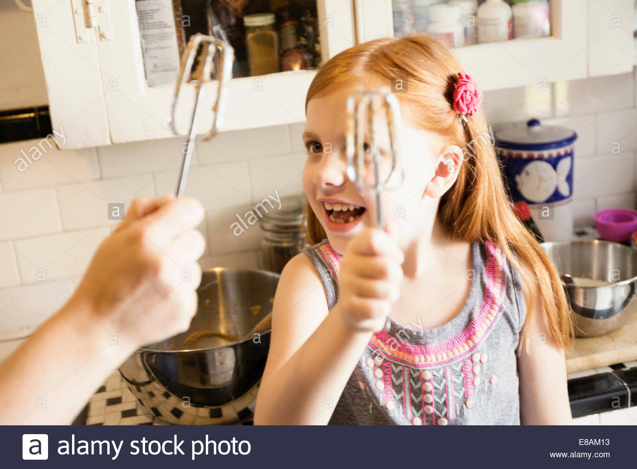 Girl and mother holding up whisks in kitchen - Stock Image