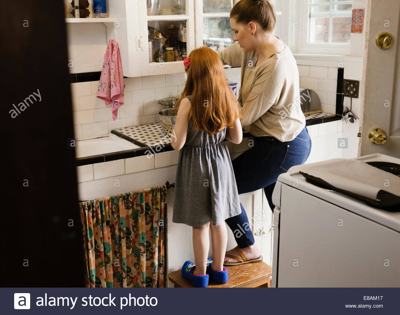 Girl and mother baking together in kitchen - Stock Image