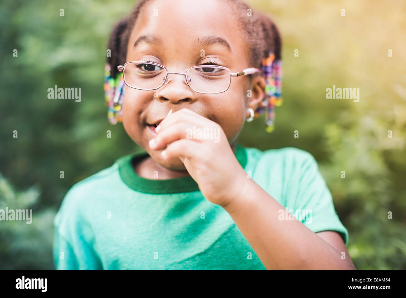 Girl smelling plant in parkland eco camp - Stock Image