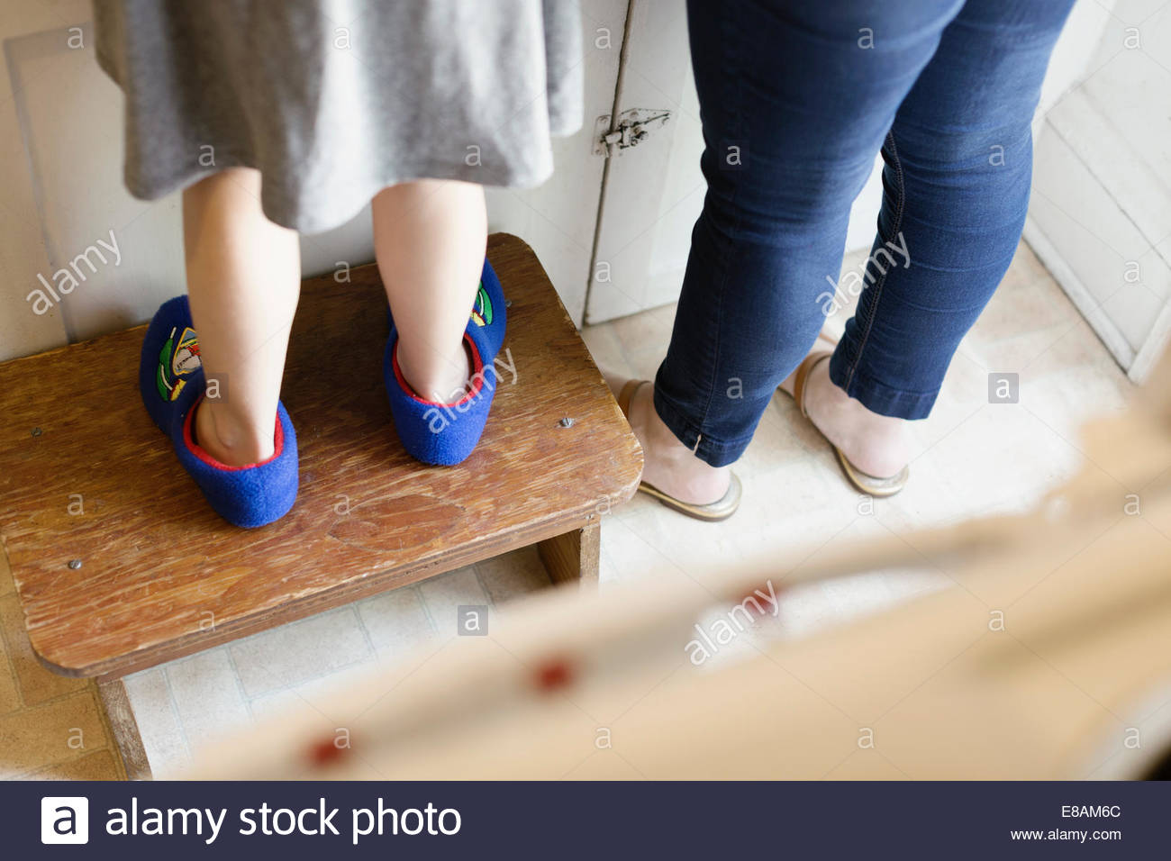 Legs of mid adult mother next to daughter standing on stool in kitchen Stock Photo