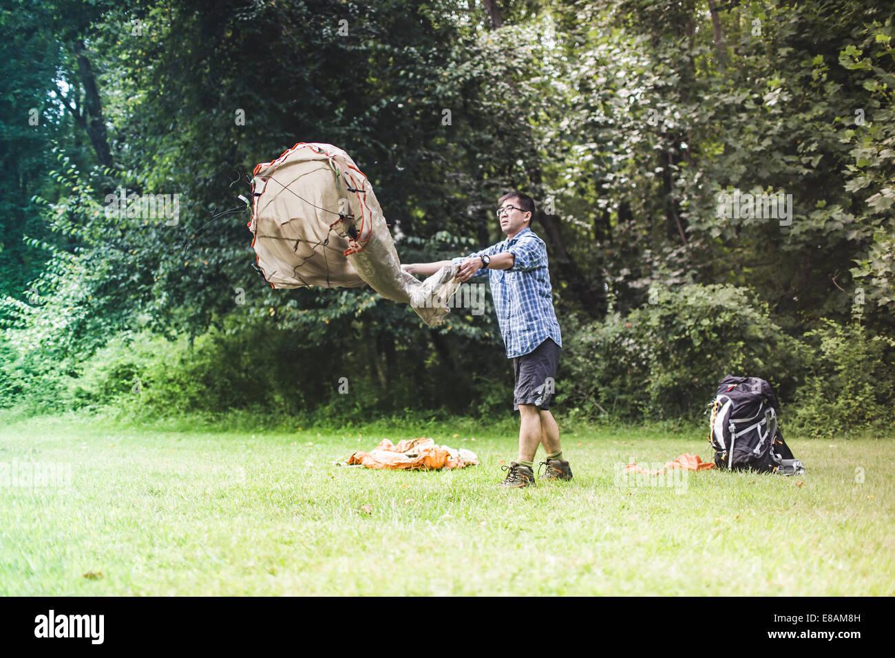 Mature man putting up tent - Stock Image