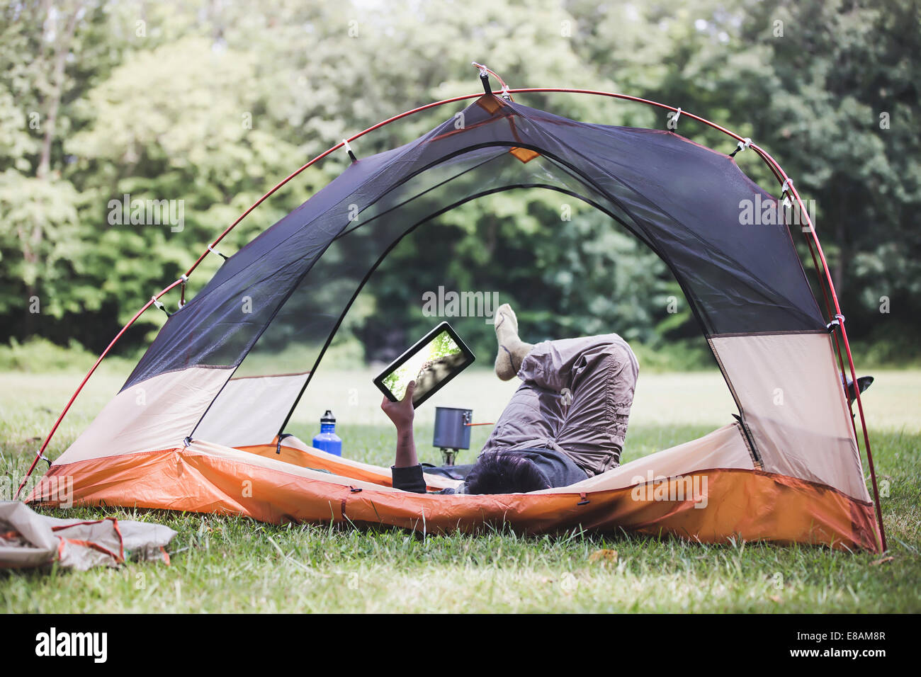 Mature man lying in tent using digital tablet - Stock Image