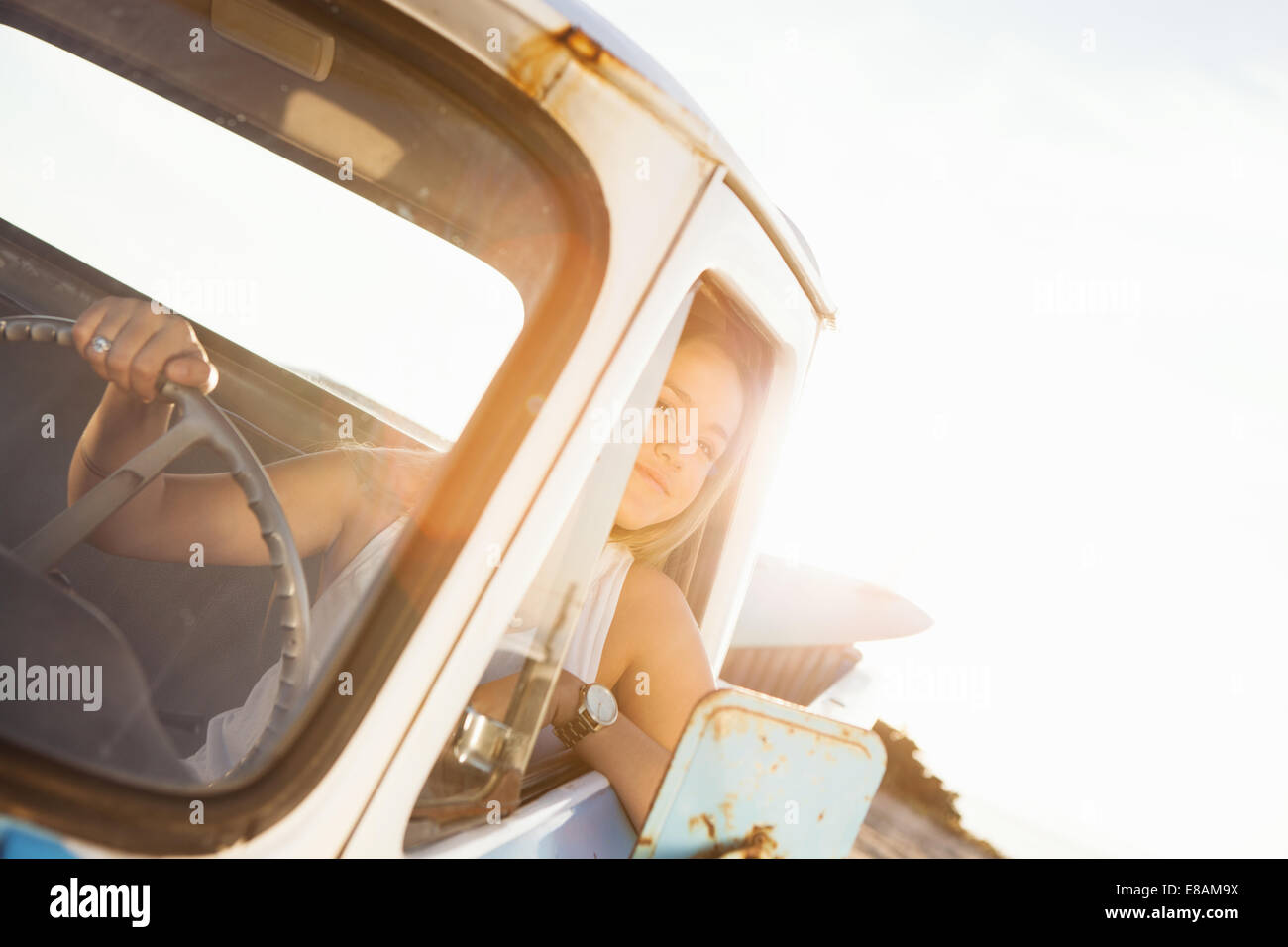 Young female surfer looking out from pickup truck window - Stock Image