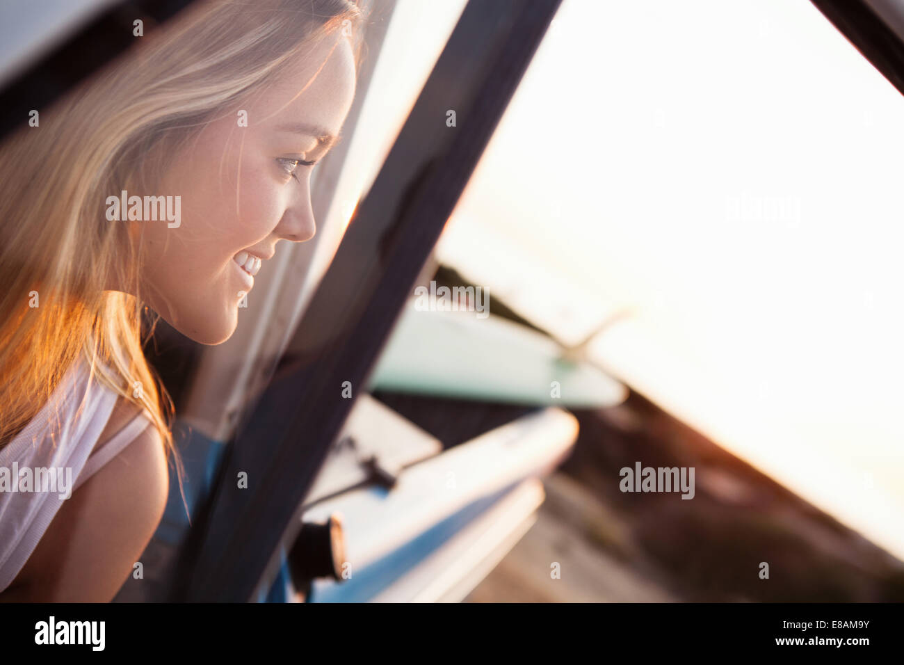 Young female surfer looking over shoulder from pickup truck at beach, Encinitas, California, USA - Stock Image