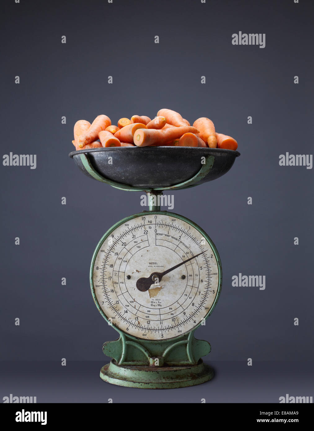 Fresh carrots on top of vintage kitchen scales - Stock Image