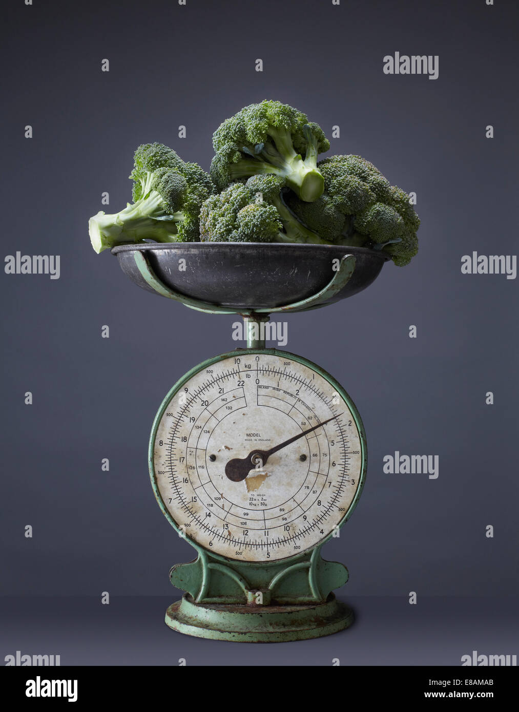 Fresh broccoli on top of vintage kitchen scales - Stock Image