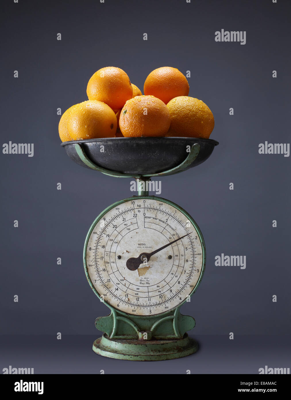 Fresh oranges on top of vintage kitchen scales - Stock Image